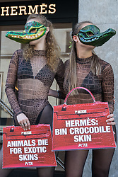 Two PETA supporters wearing Venetian crocodile masks pose outside the Hermès store in New Bond Street in protest against the luxury fashion house's use of exotic skins on 8 September 2021 in London, United Kingdom. PETA's campaign was launched following the release of video footage by The Kindness Project showing crocodiles being mutilated, electrocuted, stabbed and shot on farms in Australia with ties to Hermès and PETA are calling on the fashion brand to cease using exotic skins for their products.