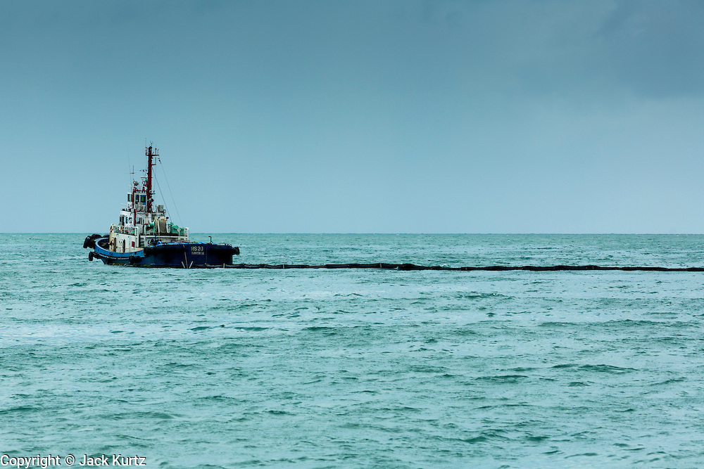 30 JULY 2013 - KOH SAMET, RAYONG, THAILAND: A cleanup ship pulls a containment boom around part of an oil spill off of Koh Samet island. About 50,000 liters of crude oil poured out of a pipeline in the Gulf of Thailand over the weekend authorities said. The oil made landfall on the white sand beaches of Ao Prao, on Koh Samet, a popular tourists destination in Rayong province about 2.5 hours southeast of Bangkok. Workers from PTT Global, owner of the pipeline, and up to 500 Thai military personnel are cleaning up the beaches. Tourists staying near the spill, which fouled Ao Prao beach, were evacuated to hotels on the east side of the island, which was not impacted by the spill. PTT Global Chemical Pcl is part of state-controlled PTT Pcl, Thailand's biggest energy firm.      PHOTO BY JACK KURTZ