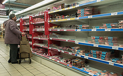 © Licensed to London News Pictures. 13/10/2021. London, UK. A shopper looks at nearly empty shelves of pre-cooked meat products in Sainsbury's, north London. This is amid fears of food shortages leading up to Christmas, due to labour shortages, following Brexit. Leading supermarkets may start rationing certain items ahead of Christmas. Photo credit: Dinendra Haria/LNP