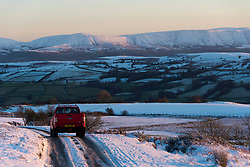 © Licensed to London News Pictures. 31/12/2020. Painscastle, Powys, Wales, UK. A motorist drives through a wintry landscape along the road between Hundred House and Painscastle in Powys during bitterly cold weather after temperatures plunged to around minus 3.5 degrees centigrade last night. Photo credit: Graham M. Lawrence/LNP