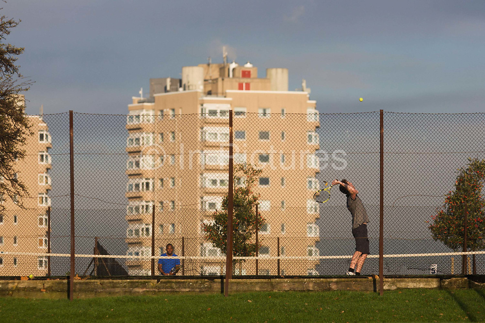 An amateur tennis player serves to a friend on the opposite side of a local court near high-rise flats seen from Brockwell Park, Herne Hill, South London. Having thrown the yellow ball up in thee air, the server pauses, before it drops and he can swing his racket to pound it across court to the waiting receiver, dressed in a blue t-shirt. The flats behind are lit in winter sunshine, warm air rising from an outlet, with only the upper floors visible to outdoor pedestrians. Brockwell Park is a 50.8 hectare (125.53 acres) park located between Brixton, Herne Hill and Tulse Hill. Brockwell Hall house and its grounds were acquired by the London County Council (LCC) in March 1891 and opened to the public the following summer. In 1901 the LCC acquired a further 43 acres (17 ha) of land north of the original park.