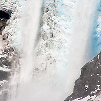 Ice falls as the Northwestern glacier calves on a summer afternoon in the Kenai Fjords National Park
