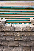 Re-roofing with reproduction Cotswold roof slates a Cotswolds stone cottage using traditional method of tiling using cardinal slates of different sizes