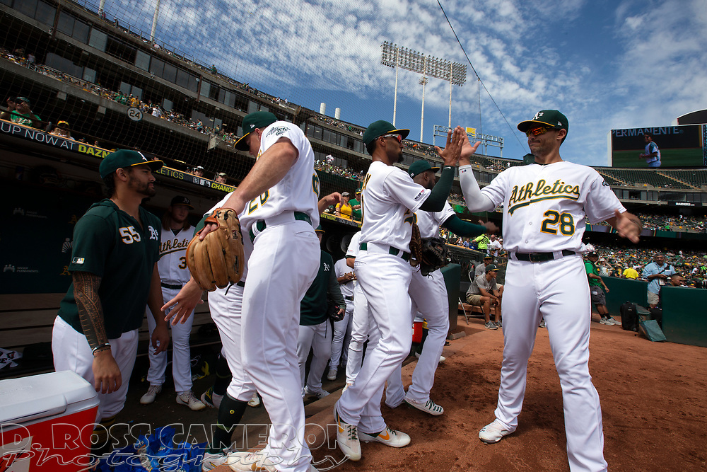 Oakland Athletics players wait to take the field for a baseball game against the Texas Rangers, Sunday, Sept. 22, 2019, in Oakland, Calif. (AP Photo/D. Ross Cameron)