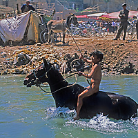 A Uygar boy rides naked and bareback in a canal to test ride horses at the Sunday Market in Kashgar (Kashi), Xinjiang, China.