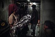 Les jeunes du clan familial emportent le corps enroulé dans une couverture vers la chambre des pleurs. - Tribu de Tendo - Hienghene - Nouvelle Calédonie - Aout 2013