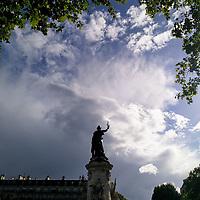 J'étais en train de rentrer chez moi, à pied comme j'aime tant le faire, quand j'ai vu, de passage sur la Place de la République, ce magnifique ciel et la statue encadrée par les feuilles des arbres. Et j'avais l'impression de voir la République debout, prête à nous protéger contre l'orage qui approchait. Le hasard a fait que je voyais cette scène un 8 mai. Un symbole trop fort ? Probablement, mais j'aime toujours autant cette photo.<br /> <br /> I was on my way walking back home, still my favourite way to go through Paris, when I saw, as I was crossing Place de la République, this beuatiful sky and the statue, framed by tree leaves. And I thought I was witnessing Republic standing ready to protect us against the coming storm. As chance would have it, the day was the 8th of May. Too strong a symbol? Probably is, but I still love this photo.