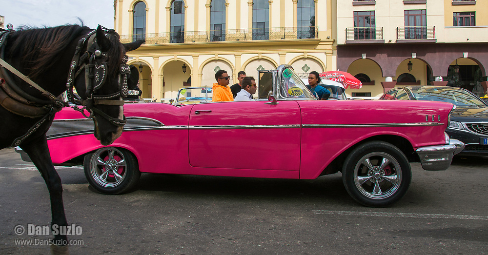 Havana, Cuba - A horse-drawn cart passes by a taxi  in front of Hotel Parque Central. Classic American cars from the 1950s, imported before the U.S. embargo, are commonly used as taxis in Havana.