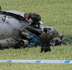 ©© licensed to London News Pictures. Andover, UK  05/07/11. Military personnel attend the scene and photograph the wreckage. A British RAF Puma helicopter pilot and two crew members escaped without serious injury today after crash-landing in a field. Police said the crewmen were able to walk away unharmed after the Puma helicopter came down close to the A303, near the Walworth industrial estate in Andover, Hampshire.. Photo credit should read Ian Forsyth/LNP