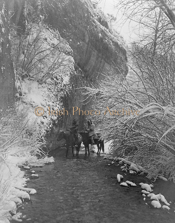 Two Crow Indians on horseback in shallow stream flanked by snow-covered trees, under rock cliff, c1908.  Photograph by Edward Curtis (1868-1952).