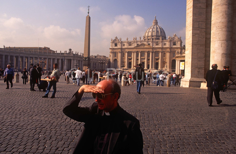 A Catholic priest shades his eyes from the sun while walking through St. Peters Square with St. Peters Basilica in the background, on 3rd November 1999, in Vatican City, Rome, Italy.