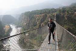 Grant Peterson on the Kusma Gyadi Bridge, the tallest (443') and one of the longest (1,128') suspension bridges in the country, on Day-7 of our Himalayan Heroes adventure riding from Tatopani to Pokhara, Nepal. Monday, November 12, 2018. Photography ©2018 Michael Lichter.