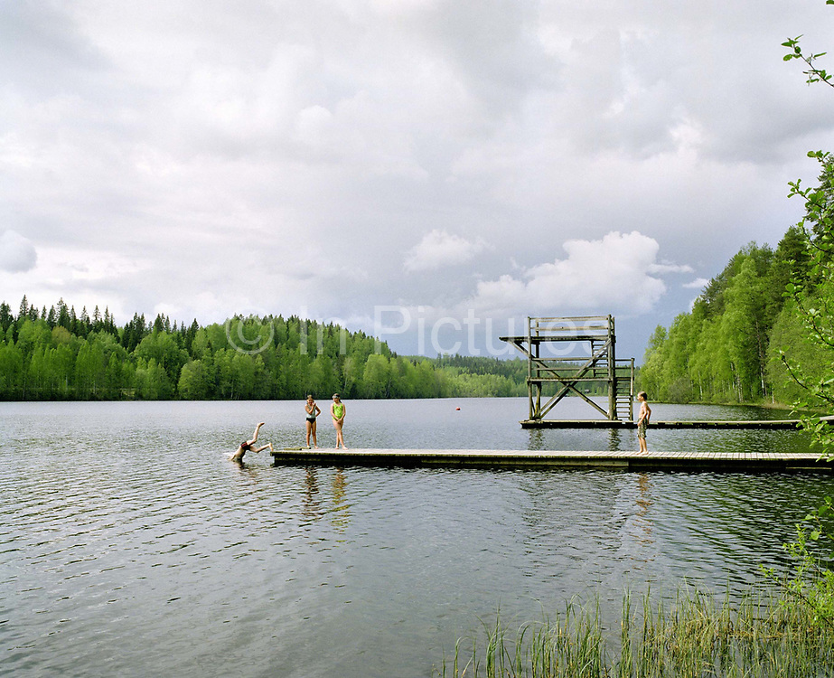 Children swimming at Lake Kohniojarvi, Jyvaskyla, Central Finland. Jyvaskyla is the capital of Central Finland and the largest city in the Finnish Lakeland, an area of more than 188,000 lakes. During the warm summer months swimming in the lake around the city is a popular activity.