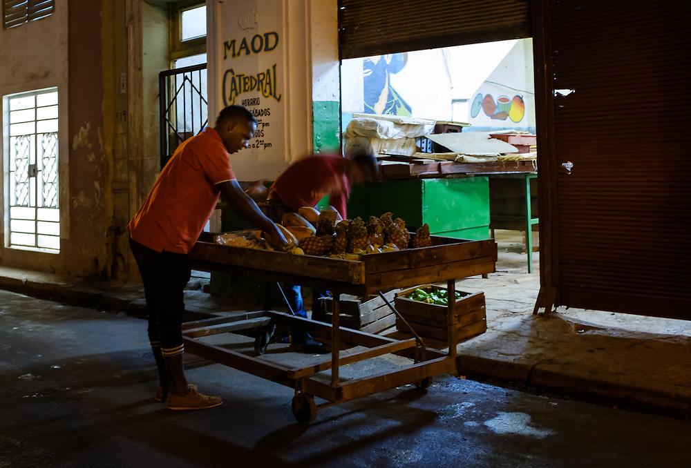 HAVANA, CUBA - CIRCA MARCH 2017:  Fruit seller at night in Havana. Men arrangung a fruit cart at night in the streets of Havana.