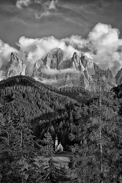 Black and white photo, tree framed St. Johann Church, Val di Funes, Dolomites mountain range, St. Magdalena, Italy.