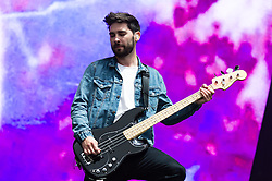 © Licensed to London News Pictures. 12/06/2015. Newport, UK.   You Me at Six  performing live at Isle of Wight Festival 2015, Day 2 Friday.  In this picture - Matt Barnes.  This afternoon has seen torrential downpours of rain after the last day of hot sunshine.   Photo credit : Richard Isaac/LNP