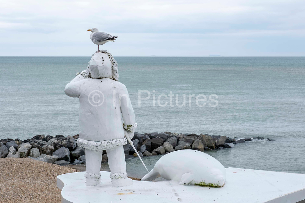 A seagull sits on The Ledge by Bill Woodrow, a sculpture on Folkestone seafront suggesting the demarcation of the rising water level resulting from the disappearing polar ice caps, depicting a human figure and a seal standing on thin ice, on the 15th of July 2021 in Folkestone, United Kingdom. The artwork builds on the work from previous triennials making Folkestone the biggest urban outdoor contemporary art exhibition in the UK.