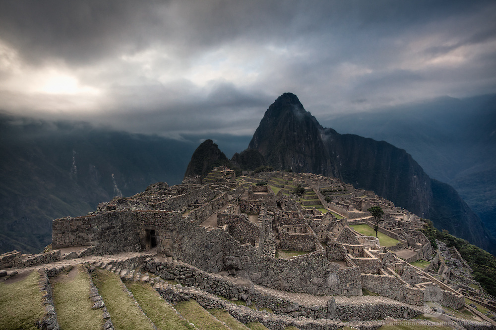 """A dramatic landscape of the famous vantage point of Machu Picchu, one of the wonders of the world and the icon of the Incan Empire. Machu Picchu is a pre-Columbian 15th-century Inca site located 2,430 metres (7,970 ft). Most archaeologists believe that Machu Picchu was built as an estate for the Inca emperor Pachacuti (1438-1472). Often referred to as the """"Lost City of the Incas."""" Wayna Picchu is the peak that sits in  the background as also has ruins on it."""