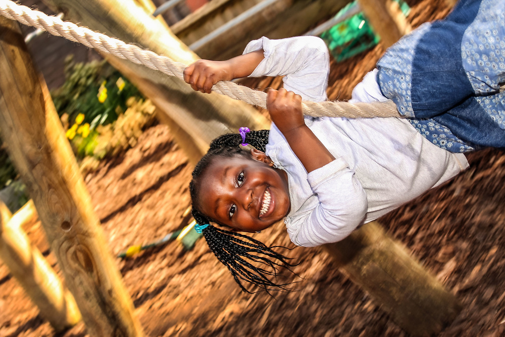 Outdoor play, young toddler playing on rope swing.<br />Clyde Early Childhood Centre<br />Deptford