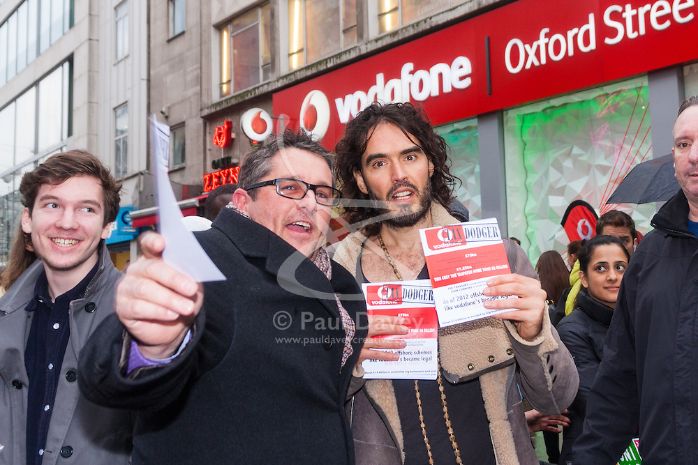 """Oxford Street, London, December 5th 2014. Actor and Comdeian turned political activist Russel Brand visits several big brands'  stores including Boots, Apple and Vodafone in London accusing them of dodging tax whilst those most in need of benefits are facing cuts and increased hardship. A leaflet being distributed by him claims £14 billion is lost every year, through tax avoidance and loopholes exploited by big business. PICTURED: A member of the public poses with Russel Brand and his leaflets that accuse Vodafone of being a """"Tax Dodger""""."""