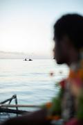 Man in traditional dress on Canoe at sunrise, Mclaren Harbour, Tufi, Cape Nelson, Oro Province, Papua New Guinea