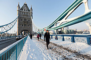 People walk across a snow covered Tower Bridge in London, England on February 28th, 2018. Freezing weather conditions dubbed the Beast from the East have brought snow and sub-zero temperatures to the UK.