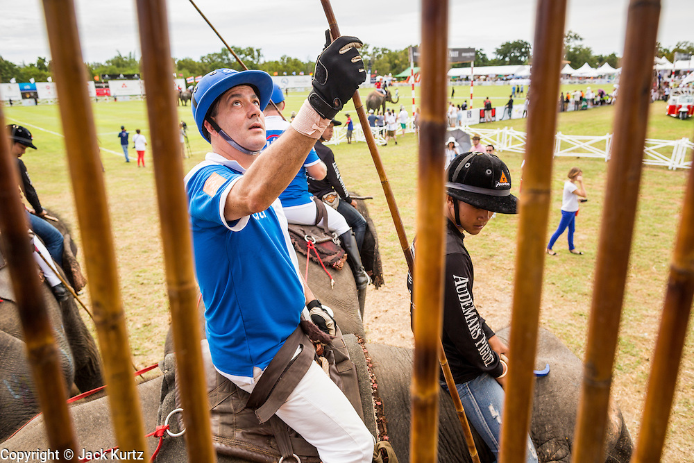 """29 AUGUST 2013 - HUA HIN, PRACHUAP KHIRI KHAN, THAILAND: DARREN BUCKLEY, of the Citibank team, picks his mallet before playing the Sata Story Design team. Citibank lost to Sara Story in the King's Cup Elephant Polo Tournament in Hua Hin. The tournament's primary sponsor in Anantara Resorts and the tournament is hosted by Anantara Hua Hin. This is the 12th year for the King's Cup Elephant Polo Tournament. The sport of elephant polo started in Nepal in 1982. Proceeds from the King's Cup tournament goes to help rehabilitate elephants rescued from abuse. Each team has three players and three elephants. Matches take place on a pitch (field) 80 meters by 48 meters using standard polo balls. The game is divided into two 7 minute """"chukkas"""" or halves. There are 16 teams in this year's tournament, including one team of transgendered """"ladyboys.""""    PHOTO BY JACK KURTZ"""
