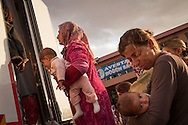 Syrian women queue outside a mobile medical facility set up outside a former wedding hall which currently hosts hundreds of displaced people fleeing Islamic State militants approaching their hometown of Kobane/Ayn al-Arab. Suruç, southern Turkey.