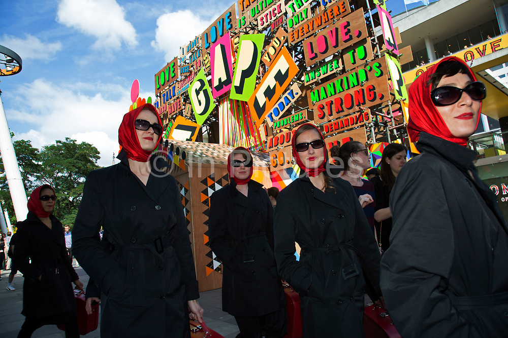 Five women wearing red headscarves pass the Festival of Love installation. The South Bank is a significant arts and entertainment district, and home to an endless list of activities for Londoners, visitors and tourists alike.