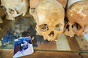 """30 JANUARY 2013 - CHEOUNG EK, CAMBODIA: A picture of Jesus Christ left by a tourist next to human skulls on display in the Buddhist stupa at the Choeung Ek killing fields. Choeung Ek is a former orchard and Chinese cemetery about 17 km south of Phnom Penh, Cambodia. It is the best-known of the """"Killing Fields"""", where the Khmer Rouge regime executed over one million people between 1975 and 1979. Mass graves containing 8,895 bodies were discovered at Choeung Ek after the fall of the Khmer Rouge regime. Many of the dead were former political prisoners who were kept by the Khmer Rouge in their Tuol Sleng detention center, a former high school in Phnom Penh.      PHOTO BY JACK KURTZ"""