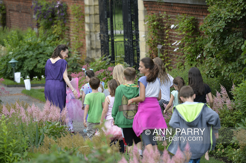 Old Westbury, New York, USA. 28th June 2015. LORI BELILOVE, dressed in purple tunic at extreme left, leads children through the gardens as Lori Belilove & The Isadora Duncan Dance Company give dancing lessons to children throughout the gardens, and then perform at historic Old Westbury Gardens, a Long Island Gold Coast estate, for its Midsummer Night event.