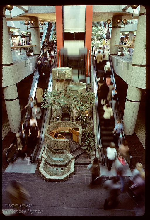 People on escalators blur past waterfalls of Town Square Park inside galleria complex; St Paul Minnesota