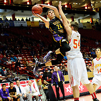 031214  Adron Gardner/Independent<br /> <br />  Kirtland Central Bronco Reese Foutz (24) shoots around Centennial Hawk Ben Hindes (54) during the state high school basketball tournament at The Pit in Albuquerque Wednesday.