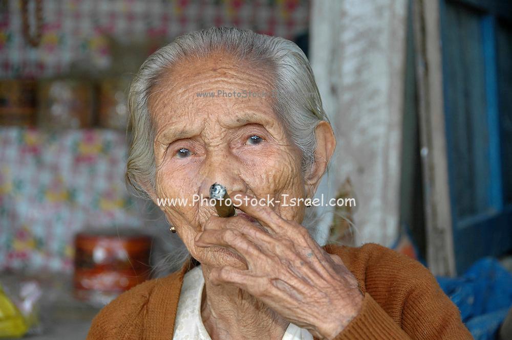 Myanmar Bagan Popa mountain park, old woman smoking a cigar