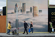 People walk beneath a property developer's billboard showing a large aerial image of London skyscrapers in low cloud. A prosperous-looking young man strides past a woman and a mother pushing a child's buggy on Shoreditch High Street. This site will be called Principal Place, a new 15-storey office block designed by Foster and Partners in Worship Street, Shoreditch, London. The mural image shows some of the capital's best-known tall buildings that rise above the fog - now a very unusual weather phenomenon after thick fogs in the 1950s.
