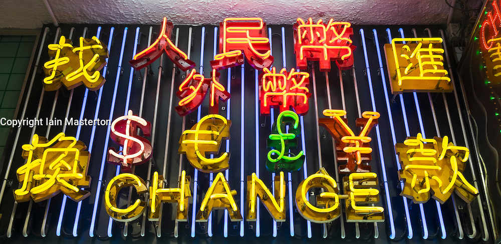 Neon lights listing various currencies above currency exchange shop at night in Hong Kong China