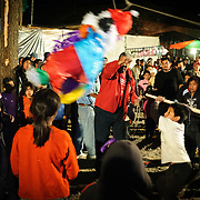 Children scamble to pick up candy and beat the pinata in front of the Church of Santo Tomas in the middle Chichicastenango, Guatemelas, as part of Convite 12 de Dicembre in Chichicastenango in celebration of the Day of Our Lady of Guadalupe.. Chichicastenango is an indigenous Maya town in the Guatemalan highlands about 90 miles northwest of Guatemala City and at an elevation of nearly 6,500 feet. It is most famous for its markets on Sundays and Thursdays.