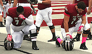 Lindenwood University - Belleville players Rafael Castillo (74, left) and Justin Kulich (73) kneel and pray before the start of their Homecoming Game against the Menlo College Oaks.