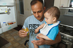 Father and son at home with baby food.