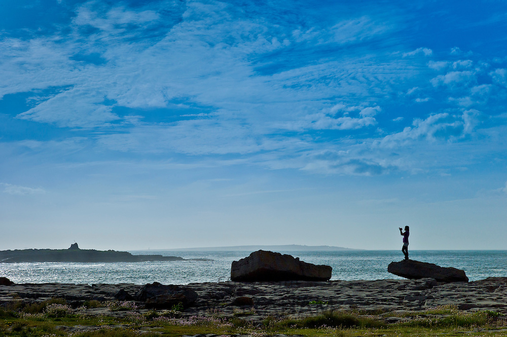 Woman taking photographs of the Arran Isles at Doolin tourist resort, County Clare, West Coast of Ireland
