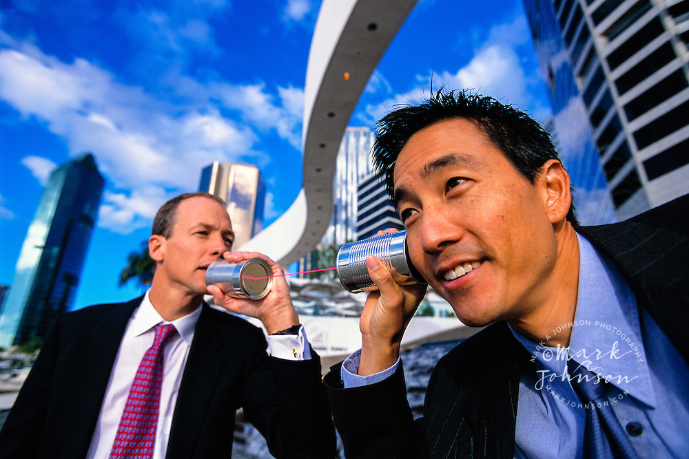 Brisbane, Australia --- Businessmen Playing with Tin Can Phone ****Model Release available