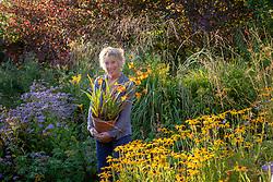 Carol Klein carrying pot of crocosmia at Glebe Cottage