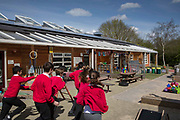 Primary school children in red uniforms run outside in their playground during break in a primary school in Oxford, England, United Kingdom.