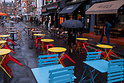 On a rainy night in Soho, tables set up for social distancing on Frith Street remain vacant at a time when recently re-opened bars and restaurants are desperate for customer business during the coronavirus pandemic, on 27th August 2020, in London, England.