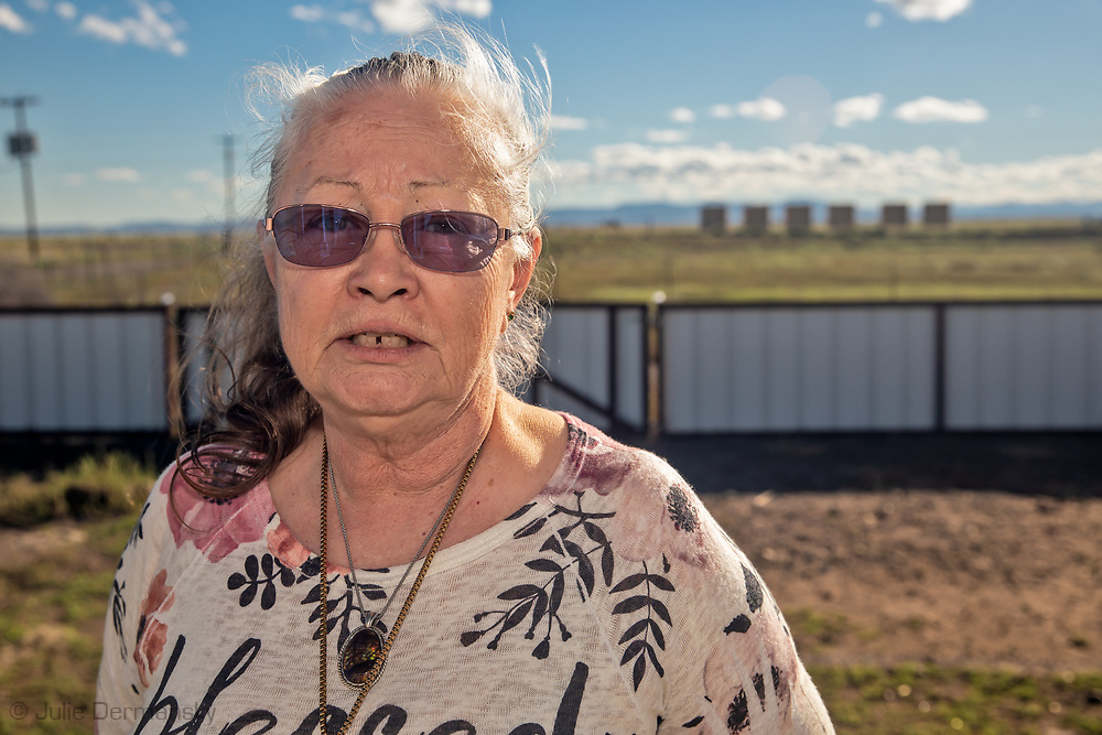 The Sue  Franklin in front of her home in Verhalen, with a fracking industry site directly across the road from them.