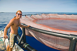 Kona Blue Water Farms worker and one of the floating open ocean fish pens which is used to raise juvenile Kona Kampachi, Hawaiian yellowtail, aka almaco jack or kahala, Seriola rivoliana, off Kona Coast, Big Island, Hawaii, Pacific Ocean