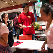 International students at USC check-in and have their papers verified before socializing amongst themselves. The staff in red shirts are also international students.
