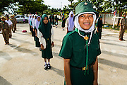 11 JULY 2013 - PATTANI, PATTANI, THAILAND:   A Thai Girl Scout watches the Thai flag get raised in the morning at the Bantaladnadklongkud School in Pattani. There are 108 students at Bantaladnadklongkud School and they are all Muslims. Five of the school's eight teachers are Buddhists.    PHOTO BY JACK KURTZ