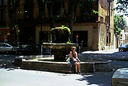 Woman sitting by water fountain in historic area of the city centre of Aix-en-Provence, France 1974