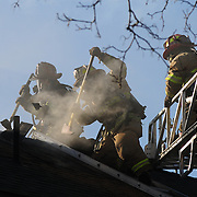 BATH, Maine -  3/30/13 - Bath Firefighters break through the roof of a home to release superheated smoke on Saturday afternoon. Fire gutted a single family home at 1270 High St in Bath on Saturday afternoon. No one was hurt. Bath Fire Chief Stephen Hinds suspected the cause was around the Luce family's wood stove chimney. It began at about 4:30 pm, while the family was out for a walk and the Bath, West Bath and Brunswick Fire depts were mopping up by 6:00. Photo for The Forecaster by Roger S. Duncan.  ..